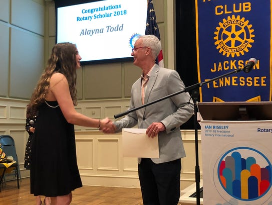 Scholarship recipient Alayna Todd shakes hands with