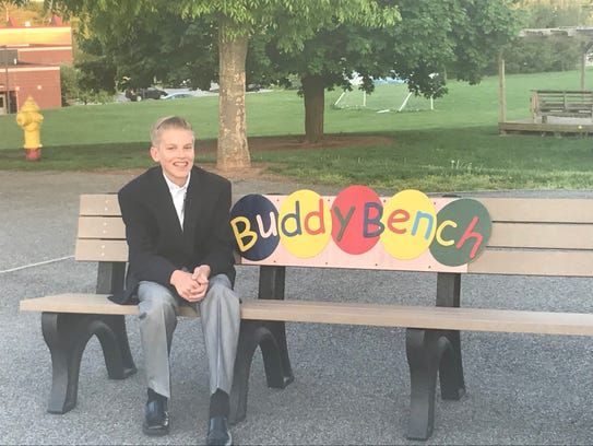 Christian Bucks, 12, is shown here sitting on a buddy bench that he promotes across the country.