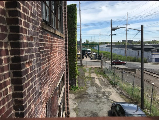 The NJ Transit Bloomfield light rail station on Grove Street in Bloomfield is seen through the second-floor steps of a fire escape to a building that once housed the manufacturer, Bakelite Corp. Friday, May 11, 2018.
