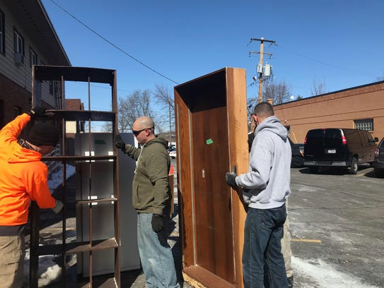 Volunteers work to move furniture out of a building