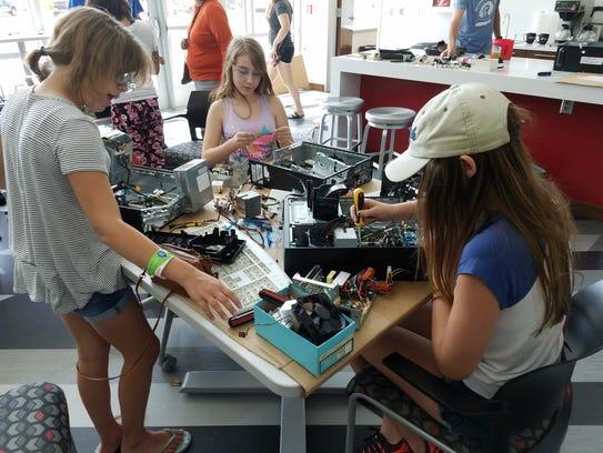 Girls take apart electronics at the first Girls Breaker