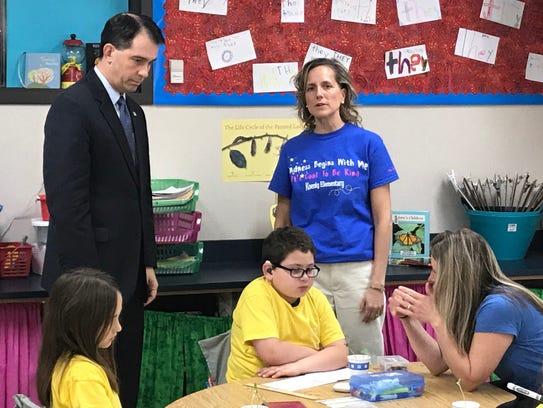 Wisconsin Gov. Scott Walker talks with a teacher while