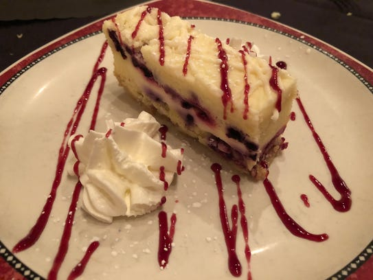 A slice of delectable, berry, key lime cheesecake at