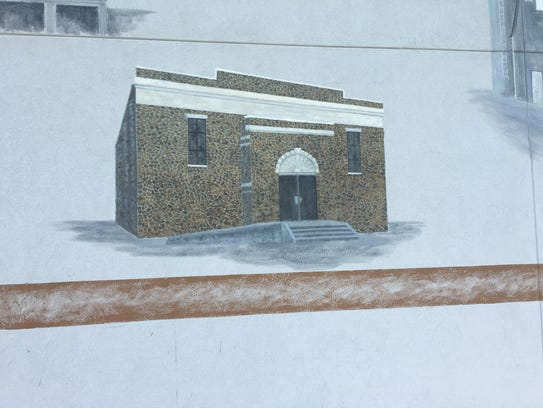 Artist Susan Loarca is painting a mural on the east