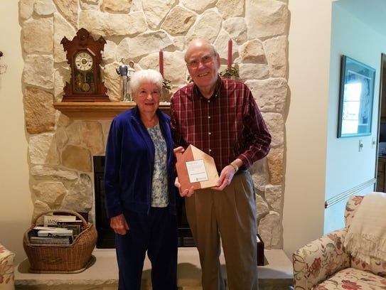 Mike and Virginia 'Ginny' McBride proudly hold their Founders Award in their Brookfield home on May 21. They were awarded for their work through Kathy's House.