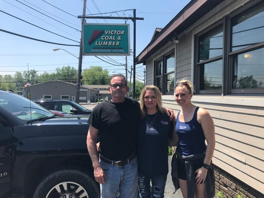 The Bliss family, from left, Michael, Tricia and Brianna, stand outside their store, Victor Coal and Lumber, which is closing on Saturday.