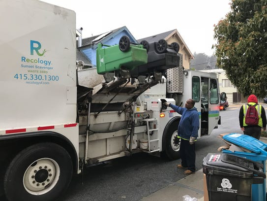 A Recology recycling truck picks up waste and mixed