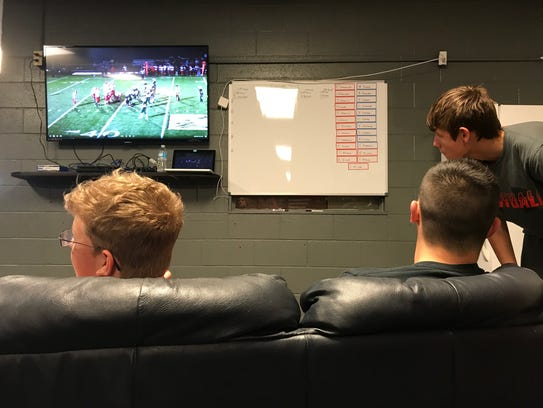 A few Elgin football players watch highlights on the
