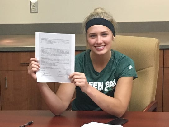 Jessica Lindstrom holds up her contract with the T71 Dudelange basketball club in Luxembourg.