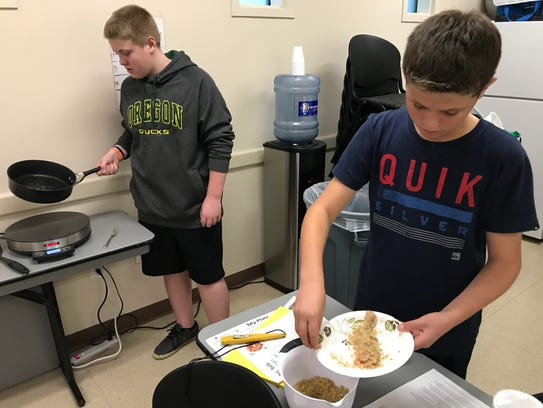 Ryder Rogers, 12, left, and his cooking partner, Lucas