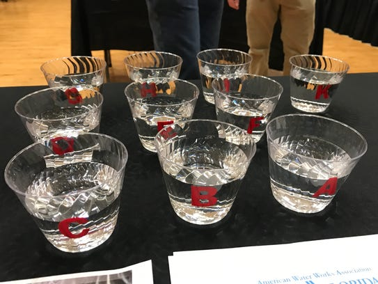 Clear cocktail cups filled with local water are labeled