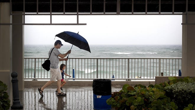 Hutch Esposito-Floyd of Lake Clark Shores shields his 3-year-old daughter from the rain at Lake Worth Beach Sunday, May 24, 2020.