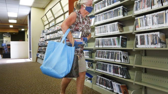 Library member Connie Devine scans titles in the DVD section of Palm Beach County's main library branch.