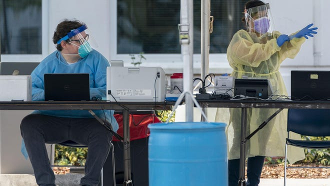 Healthcare workers prepare for patients to be tested for the coronavirus at an appointment only walk-up testing site at Lakeside Medical Center in Belle Glade, Florida on April 10, 2020 as few flights are taking off since the coronavirus pandemic.