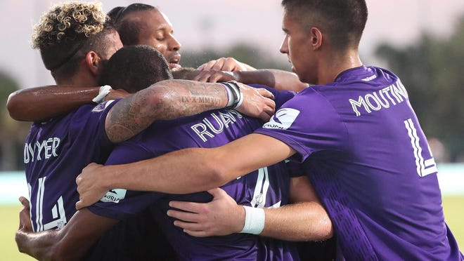 Orlando players celebrate after Chris Mueller, center,  scored a goal during the MLS is Back tournament matchup of Orlando City vs. New York City FC at ESPN Disney's Wide World of Sports complex in Orlando on July 14, 2020.