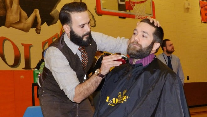 Cumberland Regional High School staff member Jordan Palmieri styles teacher Zach Grigioni's beard for the Janu-HAIRY fundraiser.