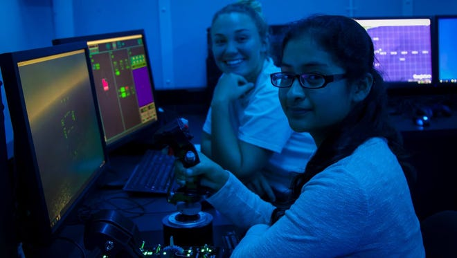 Lely High School students Avorie Anderson, left, and Jacqueline Aparicio learn at the National Flight Academy in Pensacola.