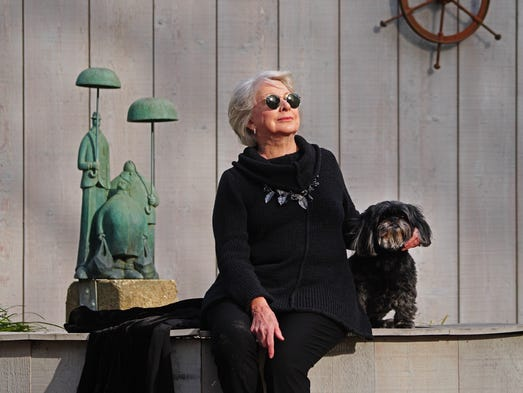 Ellen Roney Hughes sit with her dog Ming next the sculpture