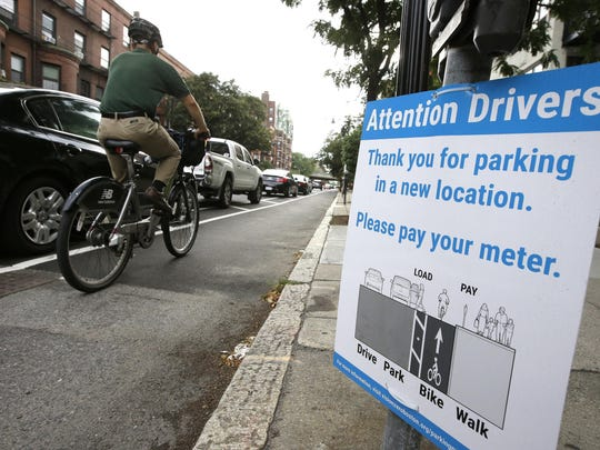 A cyclist rides in a bike lane between parked cars and the sidewalk in Boston. Cities around the world are increasingly changing bike lanes to make them safer.