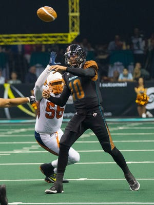 Rattlers' Nick Davila (10) throws a pass under pressure from Shock's Derrick Summers (56) during the season opener at the US Airways Center in Phoenix, AZ on March 28, 2015.