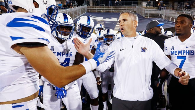 University of Memphis head coach Mike Norvell (middle) before taking the field against University of Connecticut in East Hartford, Conn., Friday, October 6, 2017.