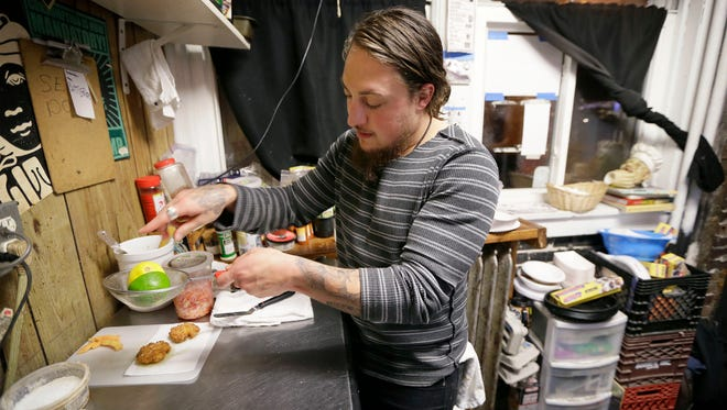 Chef Zach Gutweiler prepares panang curry fish cakes in his kitchen at the Hole in the Wall, Thursday, Nov. 13, 2014, in Des Moines, Iowa.