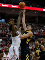 Iowa forward Luka Garza, right, goes up for a shot