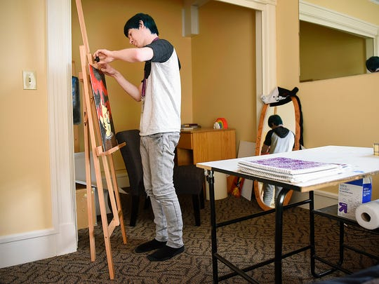 Alex Crandall shows some of his art Tuesday, May 17, at the Catholic Charities Youth House where he is living.