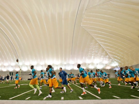 Miami Dolphins players run through drills inside the practice bubble during an NFL organized team activities football practice, Monday, June 2, 2014 at the Dolphins Training Facility in Davie, Fla. (AP Photo/Wilfredo Lee)