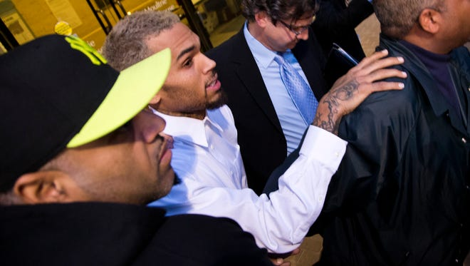 Singer Chris Brown is surrounded by bodyguards as he departs the H. Carl Moultriel courthouse on Oct. 28, 2013, with one of his attorney's, Danny Onorato, second from right, in Washington.