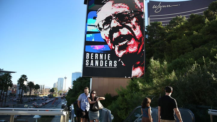 People walk past a billboard with a picture of Bernie
