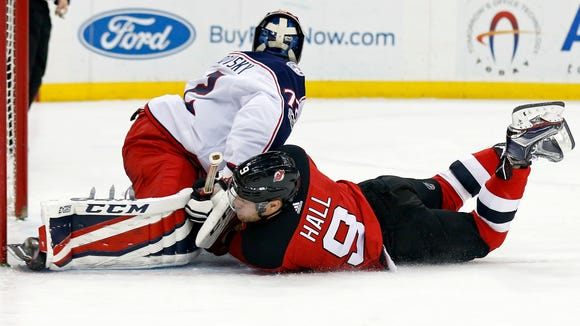 New Jersey Devils left wing Taylor Hall (9) collides with Columbus Blue Jackets goalie Sergei Bobrovsky (72) during the second period of an NHL hockey game, Friday, Dec. 8, 2017, in Newark, N.J. (AP Photo/Adam Hunger)
