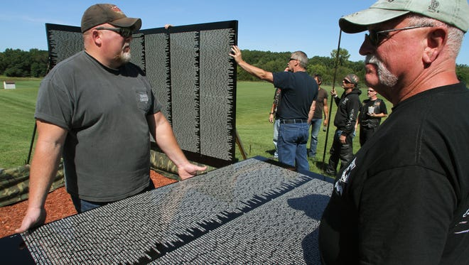 From left: John and Jeff Hendee, of Pinckney, hold a panel of The Moving Wall as volunteers at background attach the first of many panels.