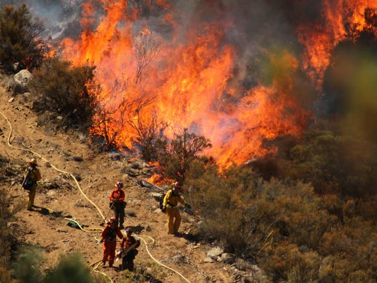 A female inmate hand crew from Puerta La Cruz and firefighters in an engine company with them set fire to reinforce the line to stave off part of the Mountain Fire burning up a hill toward them in 2013 near Lake Hemet, Calif.