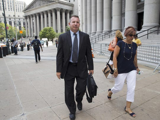 "Retired New York Police Department Sgt. Ronald Buell, center, leaves federal district court on July 13 in Manhattan. Buell received probation for selling National Crime and Information Center information to a private investigator for defense attorneys. At his sentencing, Buell said he hoped other officers would learn ""to never put themselves in the position I'm in."""