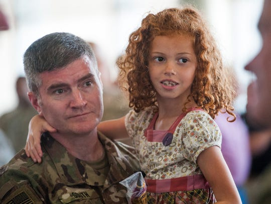 Lt. Col. Alan South holds his daughter Jenna (7) following
