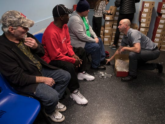 Volunteer Aaron Drury, right, helps size those in need of new shoes for a new pair of Red Wings at the Healing Place recovery facility in downtown Louisville. The Hearts to Soles event is in its 11th year in Louisville and this year 120-130 pairs of Red Wing boots were donated to those in need. Nov. 22, 2017