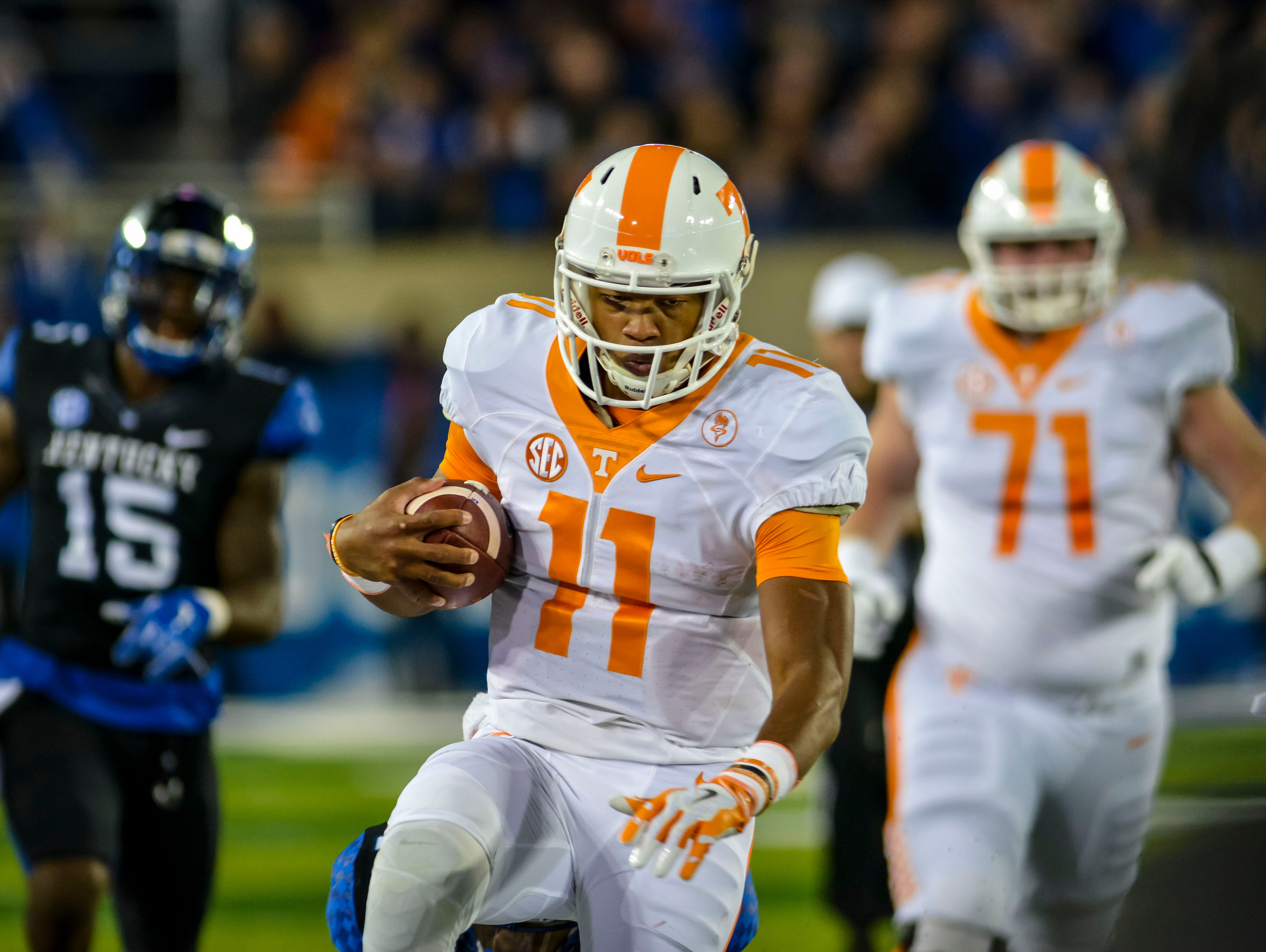Tennessee quarterback Joshua Dobbs runs out of bounds with the ball in the first quarter against Kentucky Saturday night at Commonwealth Stadium in Lexington. (October 31, 2015)