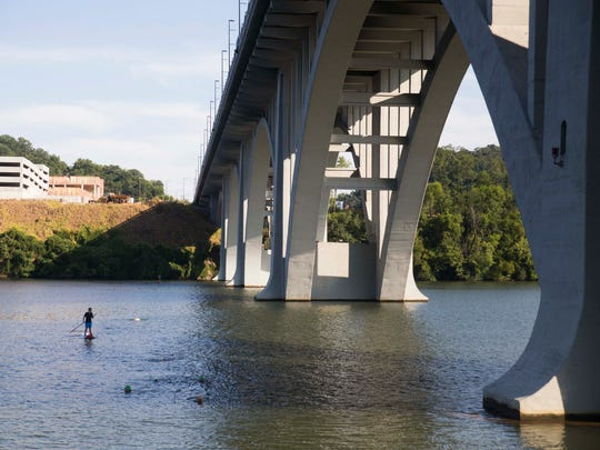 The Knoxville Open Water Swimmers swim parallel Henley Bridge in Fort Loudoun Lake near Calhoun's on the River Thursday, Aug. 3, 2017. On Sept. 17, the group will hold the inaugural Bridges to Bluffs Open Water Swim.