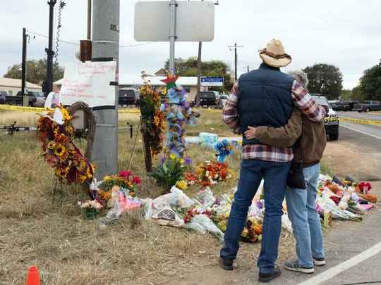 A man and woman stop and embrace at the makeshift memorial near the scene of the Sutherland Springs church shooting.