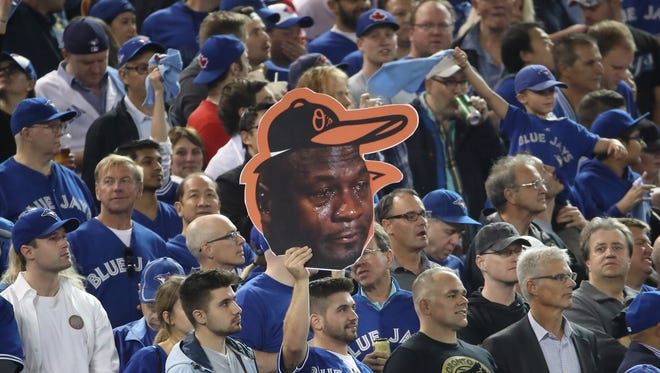 A Toronto Blue Jays fan holds up a cardboard cutout of the crying Michael Jordan meme before the start of the game against the Baltimore Orioles in the American League Wild Card game at Rogers Centre on October 4, 2016 in Toronto, Canada. (