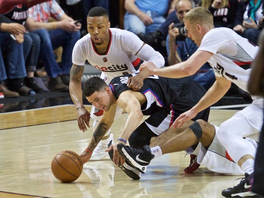 Los Angeles Clippers guard J.J. Redick, center, Portland Trail Blazers guard Damian Lillard, top, and center Mason Plumlee, right, dive for a loose ball during the second half of Game 4 of an NBA basketball first-round playoff series Monday, April 25, 2016, in Portland, Ore. (AP Photo/Craig Mitchelldyer)