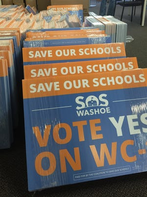 About 1,500 yard signs for the Save Our Schools campaign are stacked on the floor at campaign headquarters in Downtown Reno