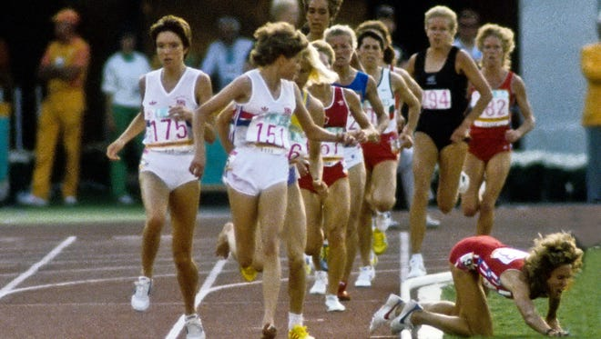 Mary Decker falls into the infield after colliding with Zola Budd during the women's 3000m final in the 1984 Los Angeles Olympic Games. Earlier in the race, UA's Joan Hansen (back right) also tripped and fell.