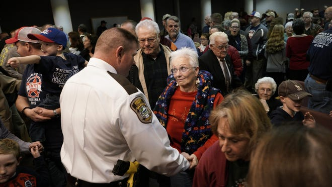 Bettina Ruleman, of Weyers Cave, who has known Donald Smith since he was in seventh grade, holds the incoming Augusta County Sheriff's hands after congratulating him following his swearing in ceremony in Verona.