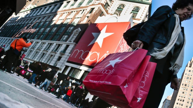 This Nov. 23 photo shows a shopper carries Macy's bags while crossing an intersection outside Macy's in New York.