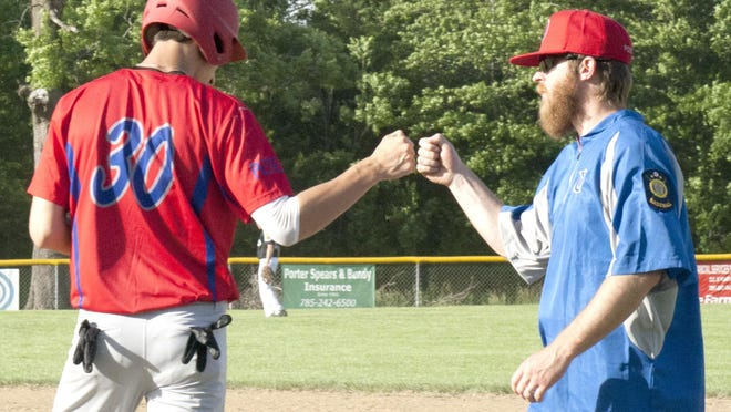 Ottawa Arrows outfielder Jose Richards fist bumps with first base coach Jordan Miller after hit in an earlier game this season. Ottawa rallied to defeat Emporia, 10-7 in eight innings, Tuesday in Emporia. [PHOTO BY GREG MAST/THE OTTAWA HERALD].