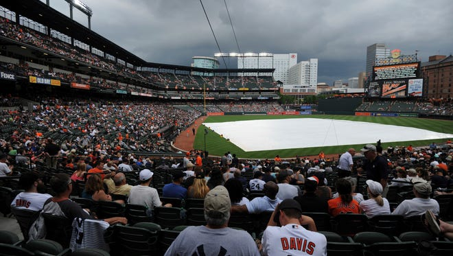 Storm clouds hover over Oriole Park at Camden Yards during a delay before the Baltimore Orioles and the New York Yankees baseball game on June 2, 2018, in Baltimore.