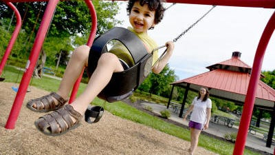 Alven Abul, 2, with his mother, Stephanie Abul of Dundee, enjoys the swings at Wolverine Park in Dundee for the first time since the play structures reopened Monday after the coronavirus shutdown.