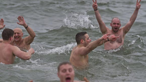The cold didn't deter these men who ran into the surf